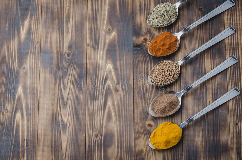 Set of various aromatic colorful spices on a wooden table. Top view and copyspace. Ingredients for cooking. Food, seasoning, cuisine, spoons, powder royalty free stock photo