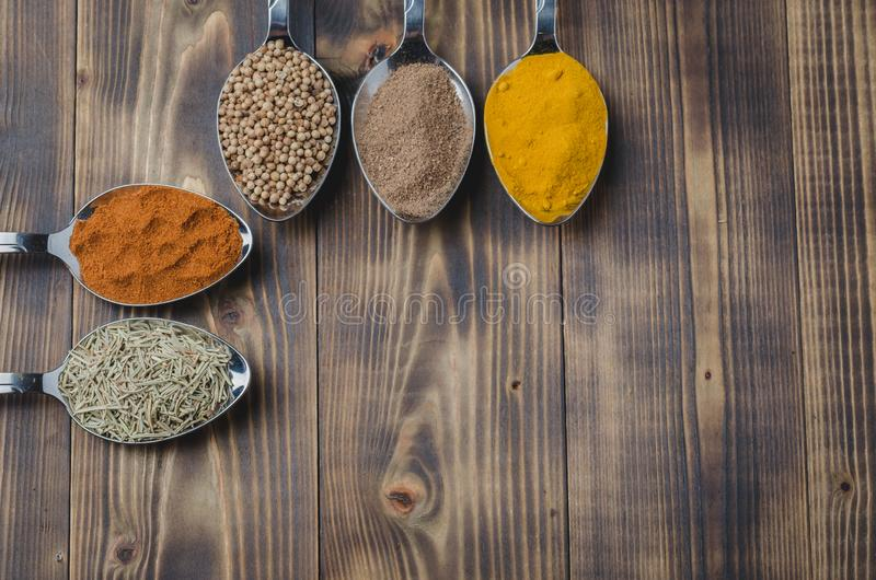 Set of various aromatic colorful spices on a wooden table. Top view and copyspace. Ingredients for cooking. Food, seasoning, cuisine, spoons, powder stock photos
