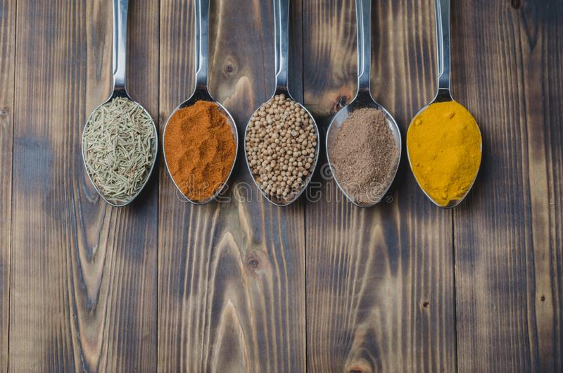 Set of various aromatic colorful spices on a wooden table. Top view and copyspace. Ingredients for cooking. Food, seasoning, cuisine, spoons, powder royalty free stock photography