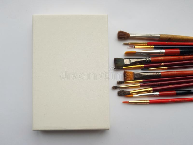 Set of various of brushes with miniature canvas on white background. Much space for text. Colored paint brushes stock photo