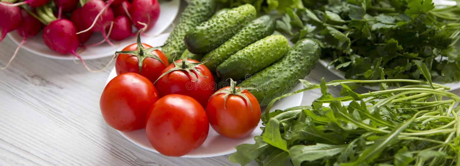 Set of various fresh ingredients for salad making: tomatoes, radish, cucumber, arugula, lettuce, side view. Healthy food concept. royalty free stock photos