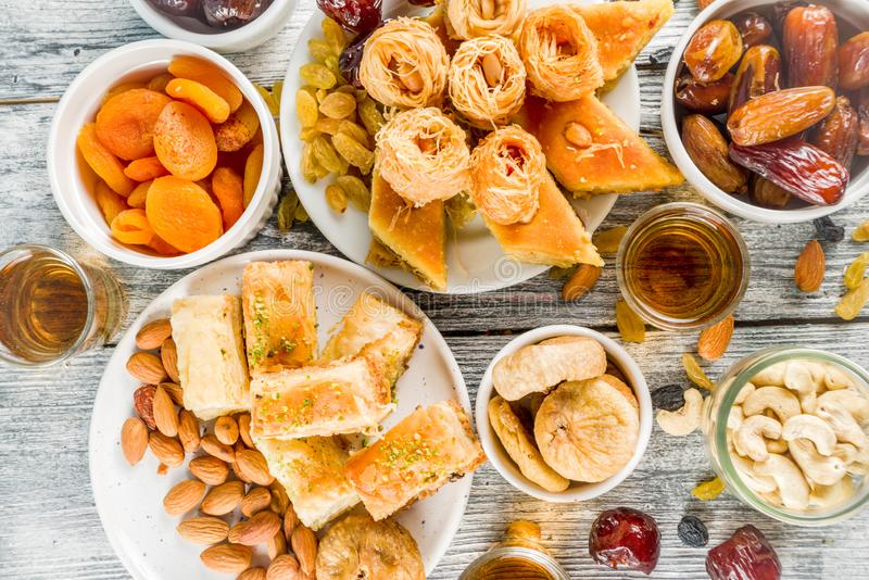 Middle Eastern Arabian sweets. Set various Middle Eastern Arabian sweets - Turkish baklava, knafeh kunaf, nuts, dried fruits and seeds. White wooden background stock image