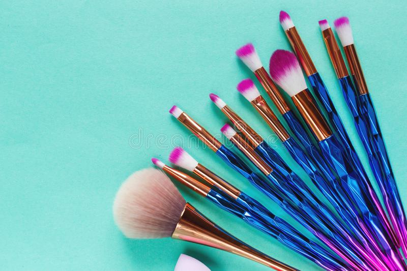 Set of various professional trendy fashion violet purple metallic makeup brushes, beauty blenders on pastel green background stock image