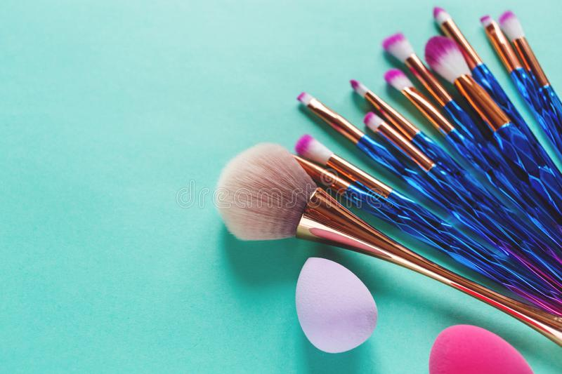 Set of various professional trendy fashion violet purple metallic makeup brushes, beauty blenders on pastel green background. royalty free stock images