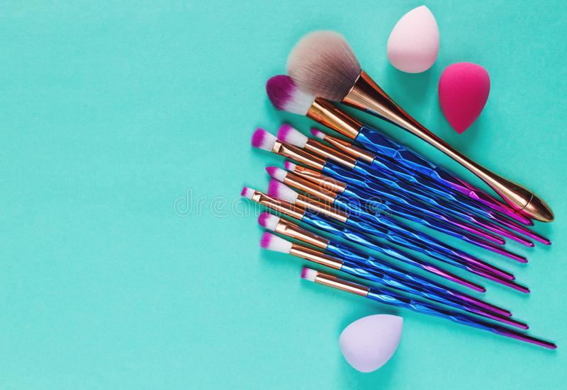 Set of various professional trendy fashion violet purple metallic makeup brushes, beauty blenders on pastel green background. royalty free stock image