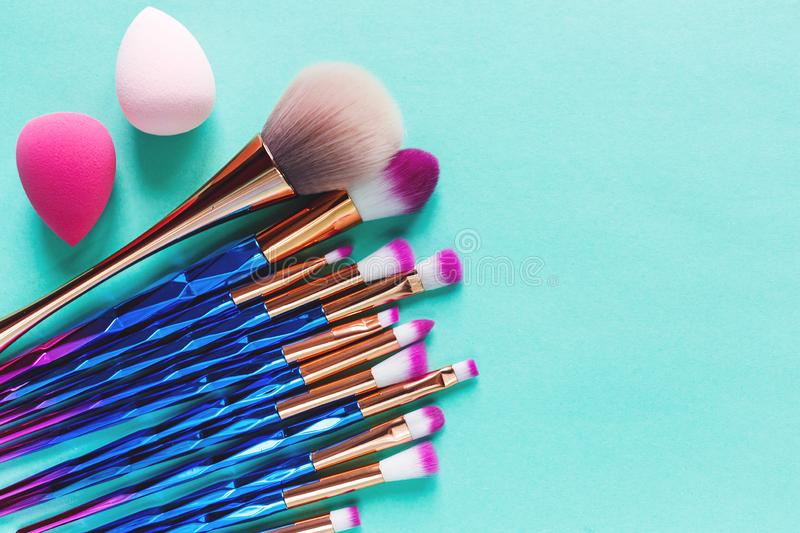 Set of various professional trendy fashion violet purple metallic makeup brushes, beauty blenders on pastel green background. royalty free stock photos
