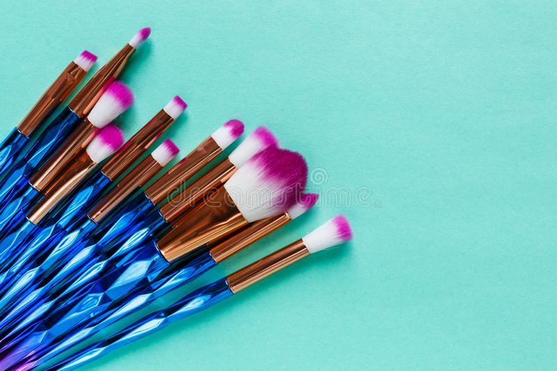 Set of various professional trendy fashion violet purple metallic makeup brushes on pastel green background. Flat lay, top view royalty free stock photography