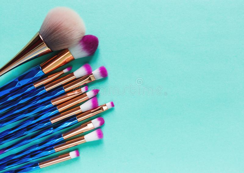 Set of various professional trendy fashion violet purple metallic makeup brushes on pastel green background. Flat lay, top view. royalty free stock photography
