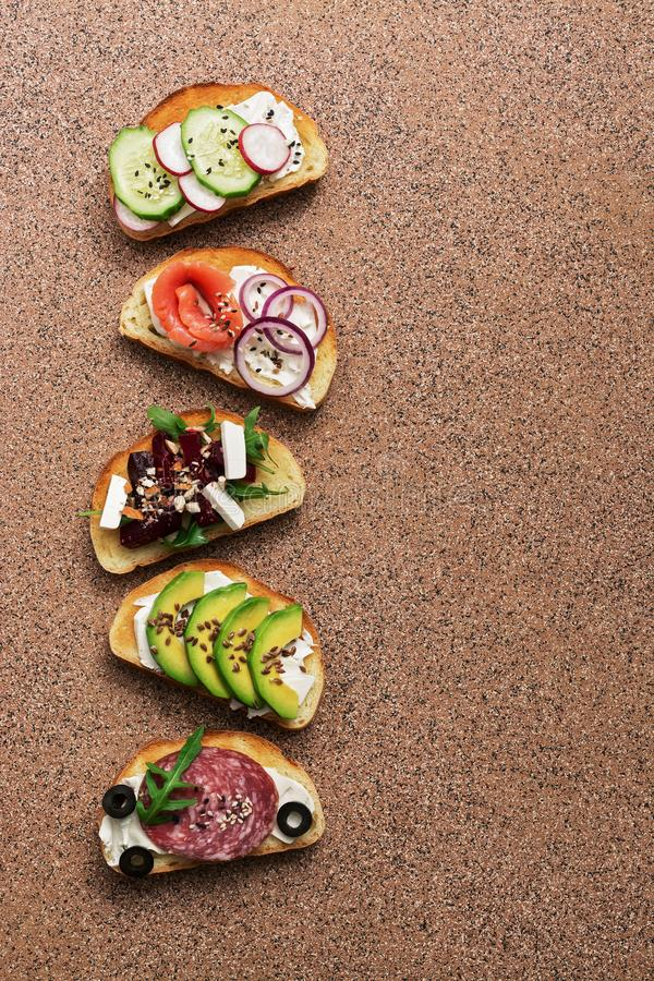 A set of various sandwiches with salmon, smoked sausage, vegetables and feta cheese on a brown stone background. Top view.  royalty free stock photos
