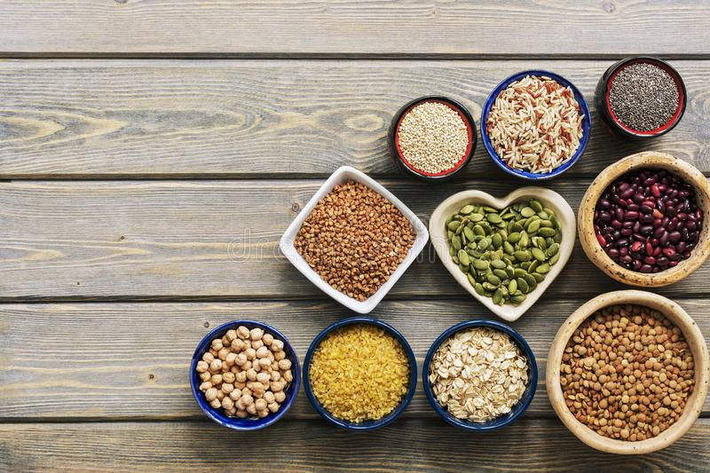 A set of various superfoods — whole grains,beans, seeds, legumes in bowls on a wooden plank table. Top view, copy space stock image