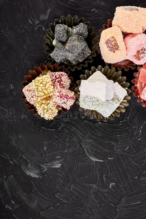 Set of various Turkish delight om black background. Top view. Flat layrMiddle Eastern dessert royalty free stock images