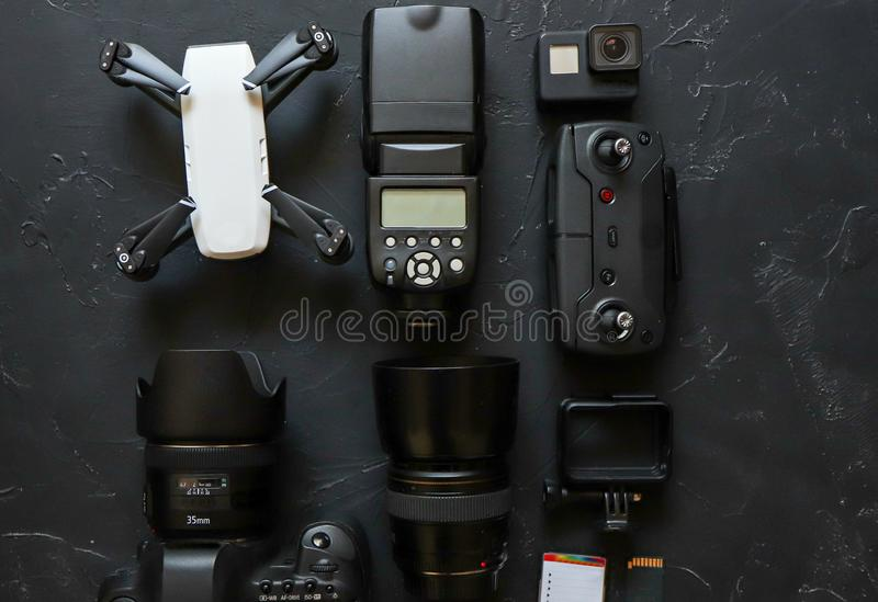 Set of videographer on a black background. Digital camera, memory card, action camera, drone, remote control and camera. Top view stock photo