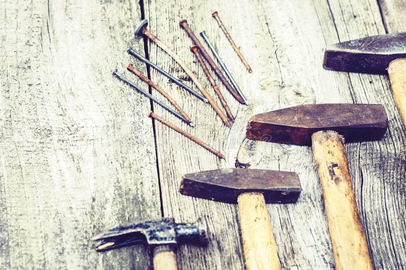 Set of vintage hand construction tools hammers with nails on a wooden background, retro concept stock images