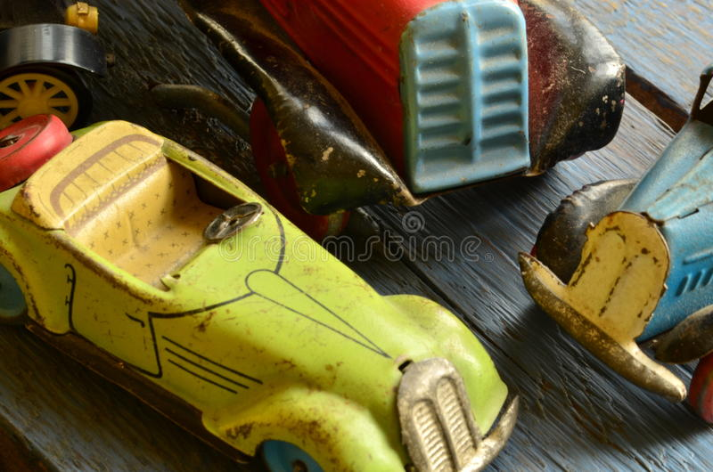 Set of vintage toys - convertible toy car, trucks (lorries) toy, post car toy and spinning (humming) tops.  royalty free stock image