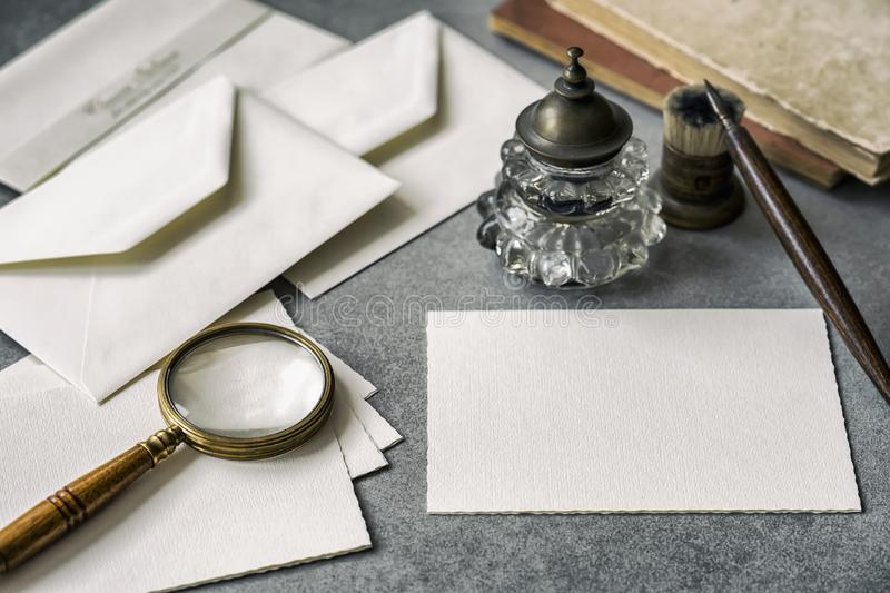 Set of vintage writing stationery items, wooden pen, inkwell, magnifier and envelopes, letters closeup. stock photography