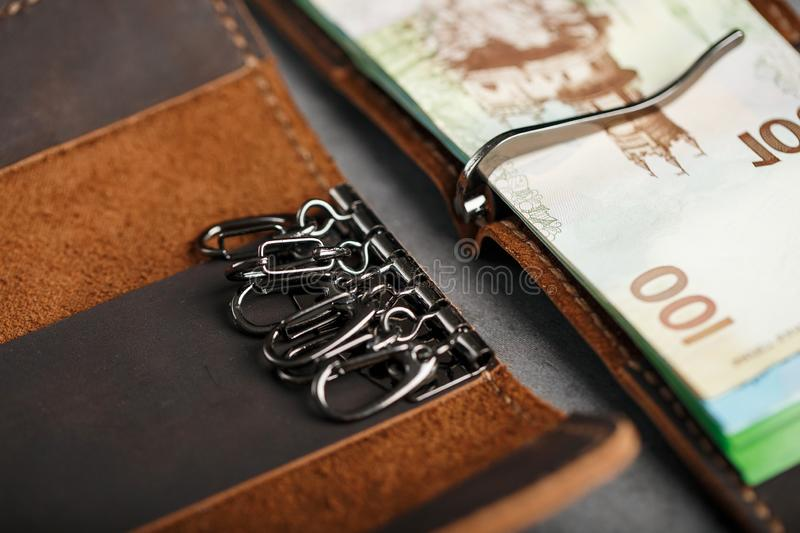 Set of a wallet with money and electronic cards and a key holder made of genuine leather of brown color, handmade on a dark. Background. Close-up royalty free stock photo