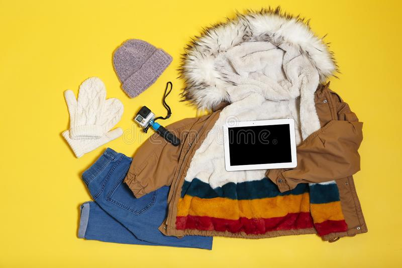 Set of warm clothes and devices on color background, flat lay. Winter vacation royalty free stock image