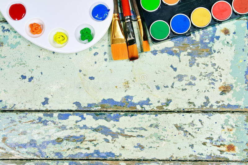 Set of watercolor aquarell rainbow paints and brushes on vintage. Wooden background. Top view stock image
