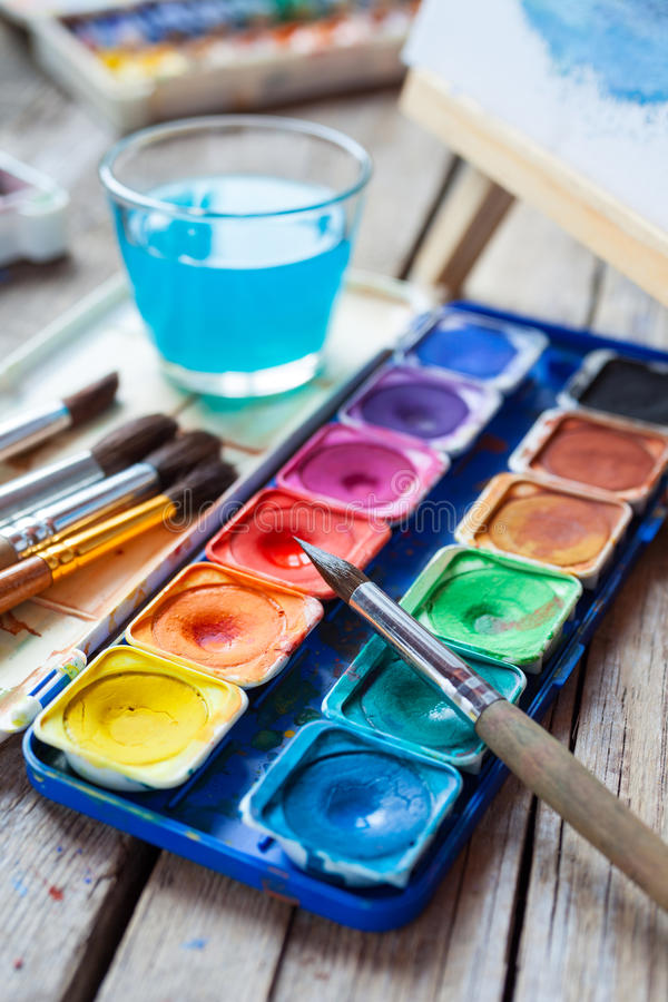 Set of watercolor paints, art brushes, glass of water and easel. With painting on vintage wooden background royalty free stock photography
