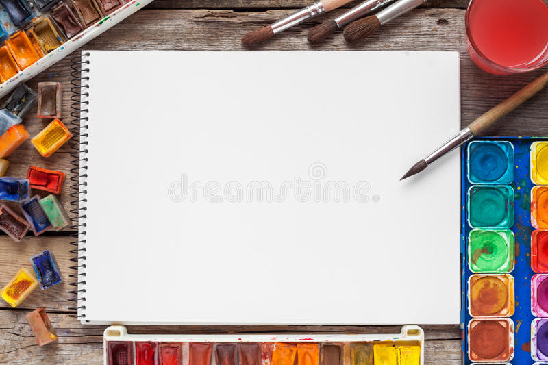 Set of watercolor paints, brushes for painting and blank white. Paper sheet of sketchbook on vintage wooden background. Top view royalty free stock photos