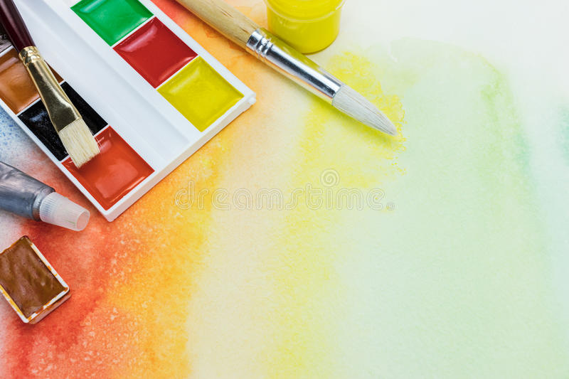 Set of watercolor paints and paintbrushes on colorful painted ba royalty free stock photo