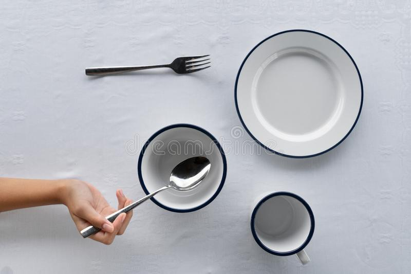 Set of white dish bowl cup on food dining table with fork and hand holding metal spoon on tablecloth background stock images