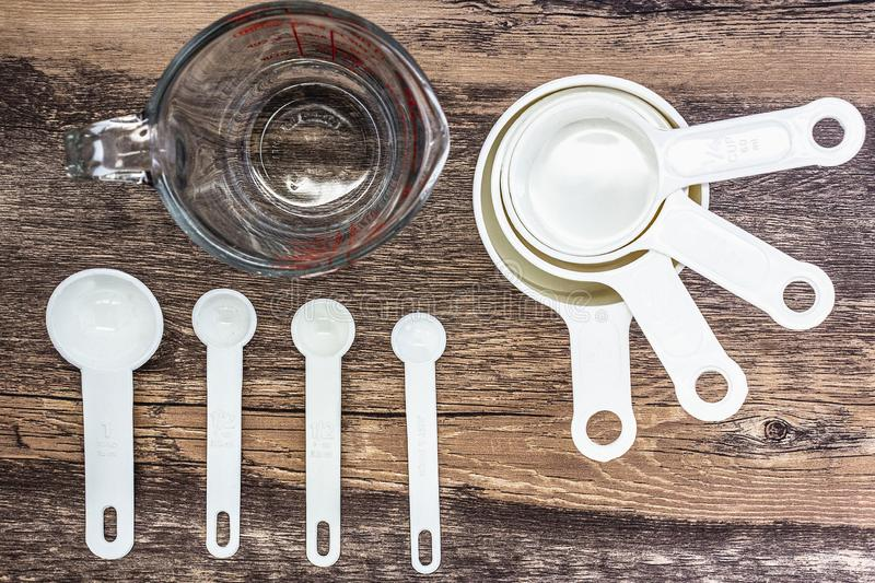 Set of white measuring cups, measuring spoons and  measuring glass use in cooking lay on wooden tabletop in top view royalty free stock images