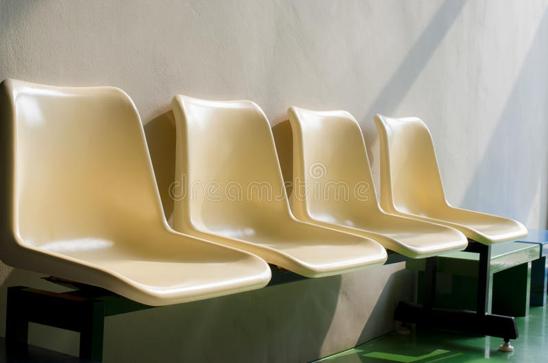 Set of white plastic chairs. Standing in front of gray cement wall. Concept image royalty free stock photo