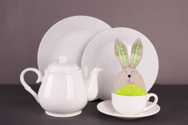 Set of white utensils for lunch and tea party and funny easter bunny on a gray background. Easter set for table service stock photography