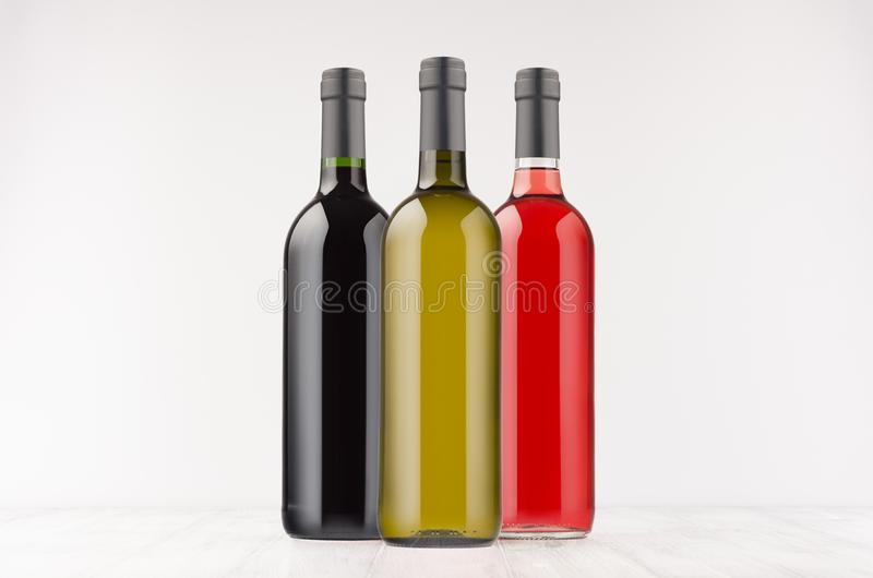 Set wine bottles different colors - red, green, black- on white wooden board, mock up. stock image