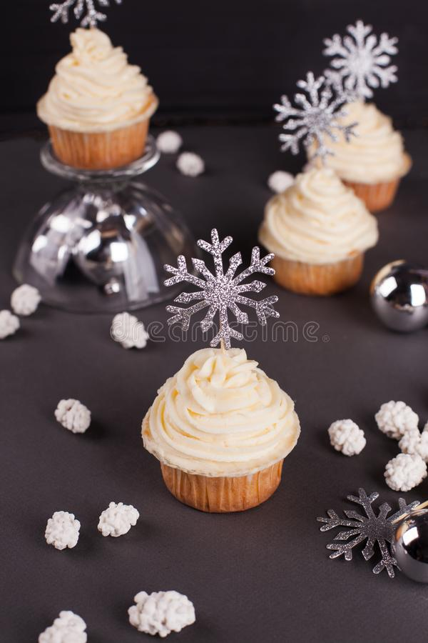 Set of winter Christmas New Year cup cakes on black background. Sweets for christmas - Christmas cupcake with cream cheese decorated with shining silver stock images