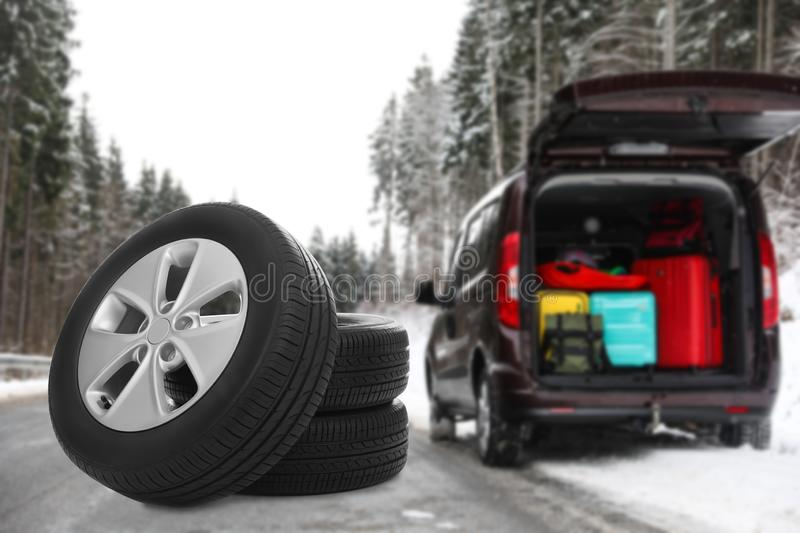 Set of winter tires near broken car with open trunk on forest highway. royalty free stock photography