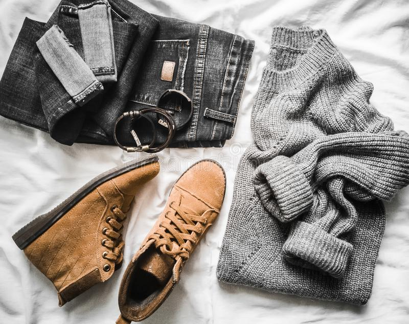 Set of women`s autumn, winter clothes on a light background - jeans, gray pullover oversize, suede brown boots and scarf. Fashion. Able clothes for walks, flat royalty free stock image