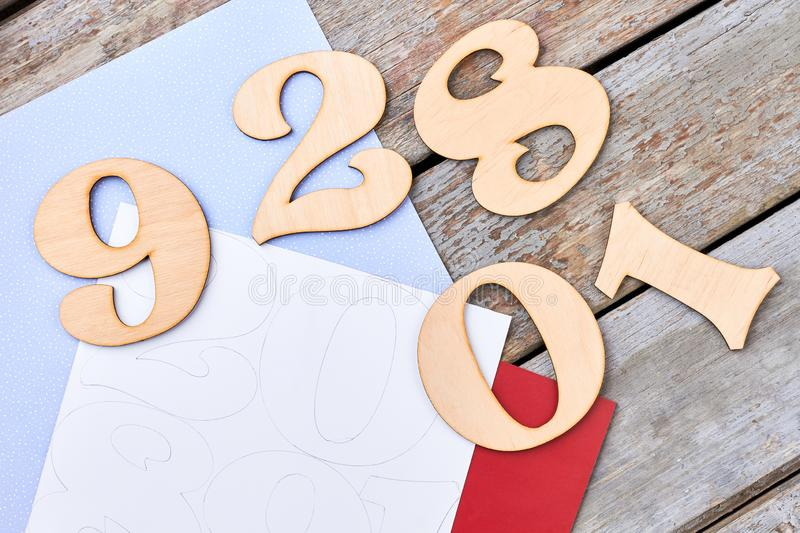 Set of wooden handmade digits, top view. Cut out wooden numbers, paper, draw template on old wooden background royalty free stock image