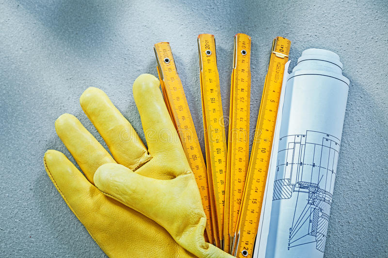 Set of working gloves construction drawings wooden meter on conc. Rete background building concept royalty free stock photo