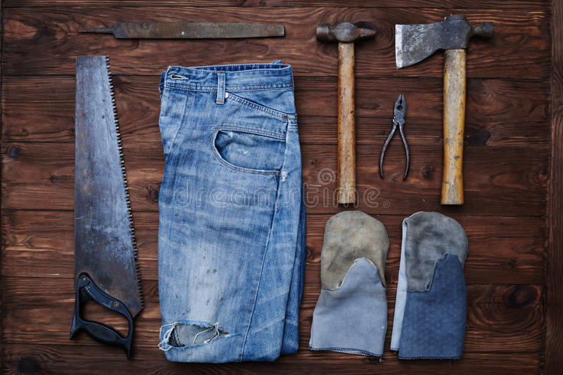 The set of working tools, gloves and jeans on a grunge background stock photography