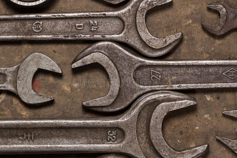 Set of wrenches on oiled floor of the garage. Wrenches of various sizes lie on the floor, huddled together royalty free stock photo