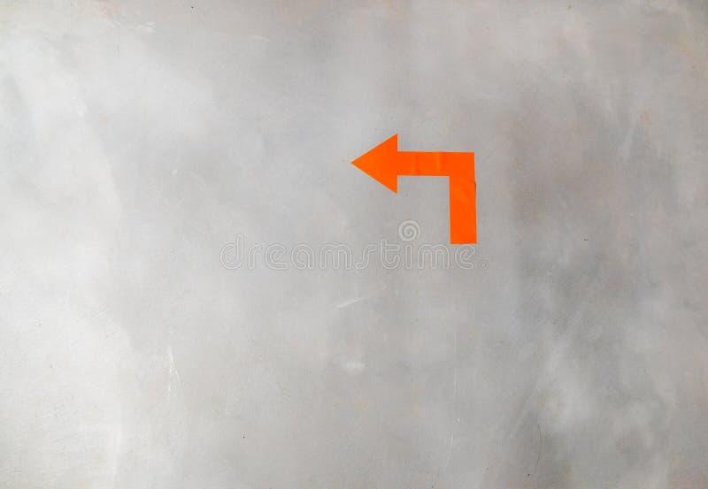 Seta alaranjada em um muro de cimento cinzento que aponta ao virar da esquina fotografia de stock