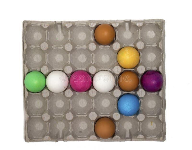 Seta criativa bonita feita de ovos coloridos em uma bandeja Ponteiro ou cursor dos ovos Vista superior e configuração lisa foto de stock