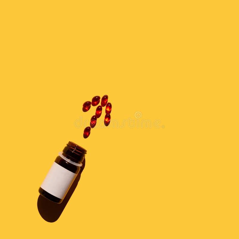 Seta das vitaminas, derramando fora de uma garrafa no fundo amarelo fotografia de stock royalty free