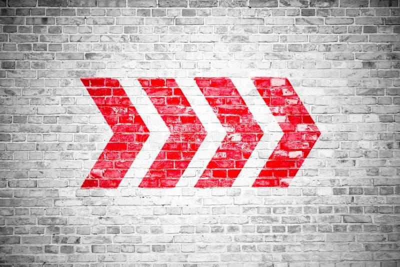 A seta direcional vermelha assina o sentido apontando pintado em um fundo cinzento branco da textura do quadro indicador da pared imagem de stock