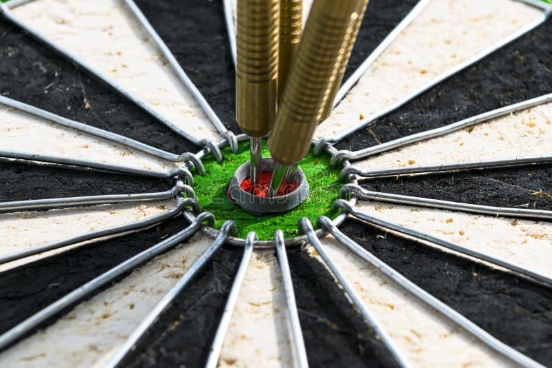 Seta dos dardos nos dardos do centro do alvo no fim do olho do ` s do touro acima Arremessa o jogo fotos de stock
