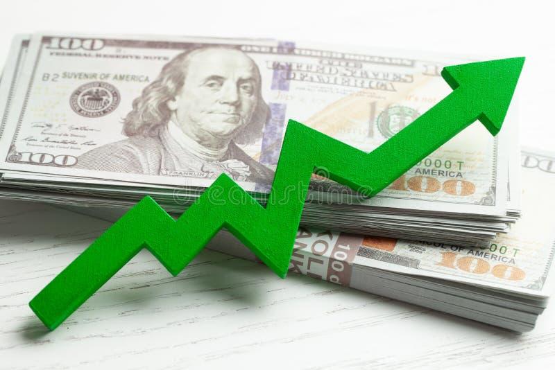 Seta gráfica verde acima e pilha de dinheiro Crescimento do lucro e do desempenho imagem de stock