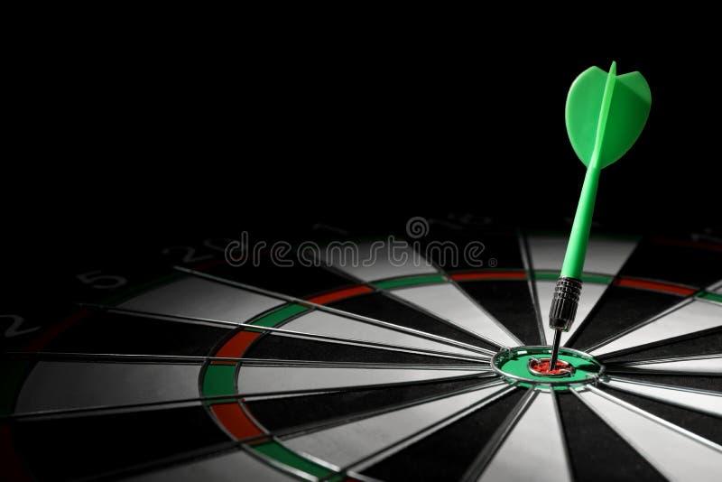 Seta verde que bate na placa de dardo contra o fundo preto Espa?o para o texto fotos de stock royalty free