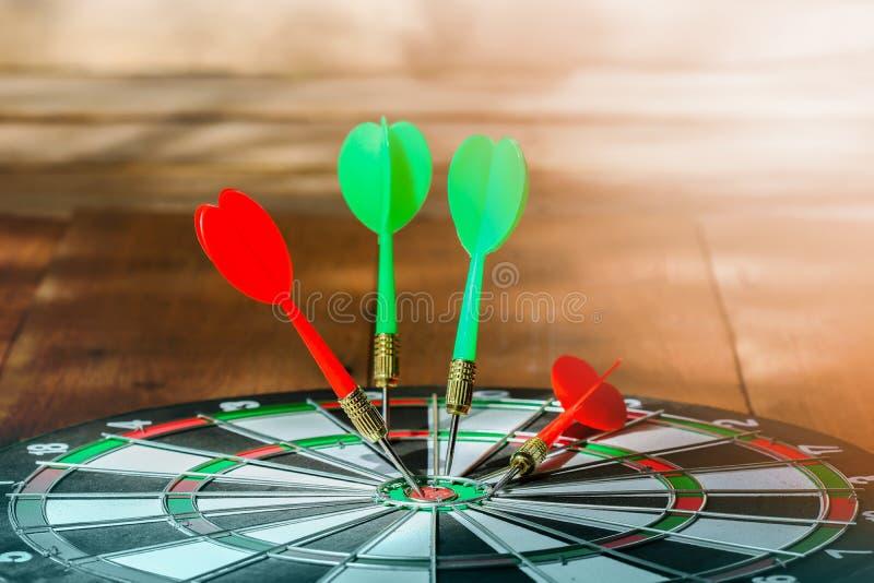 Seta vermelha e verde dos dardos no alvo do centro do alvo foto de stock