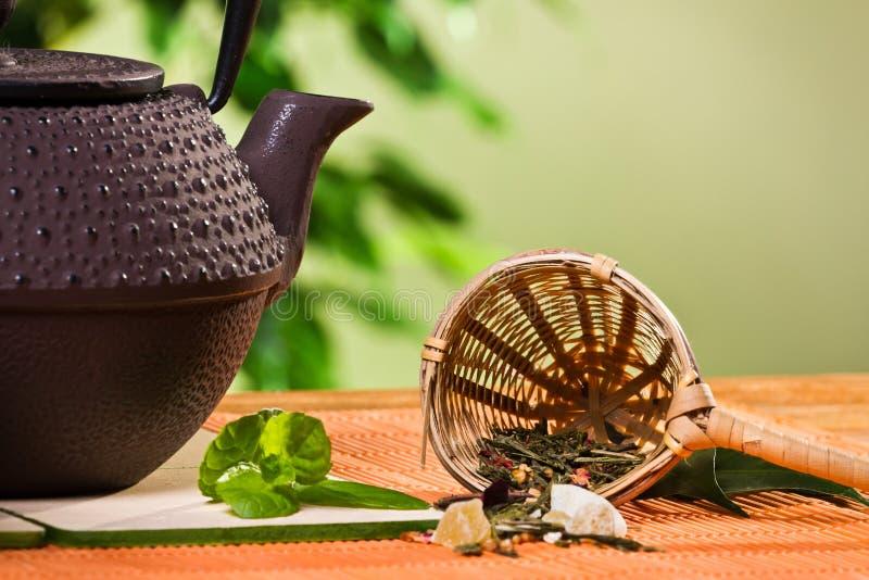 Setaccio del tè del primo piano con i fogli di menta e della teiera immagine stock