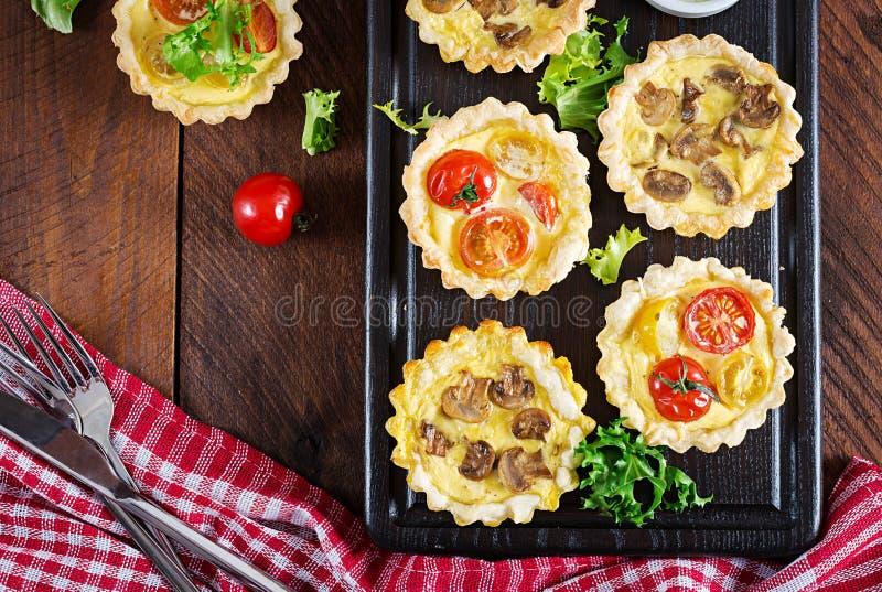 Setas, Cheddar, tartlets de los tomates en fondo de madera Mini Pies fotos de archivo libres de regalías