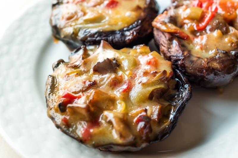 Setas cocidas de la castaña rellenas con queso y verduras derretidos imagen de archivo
