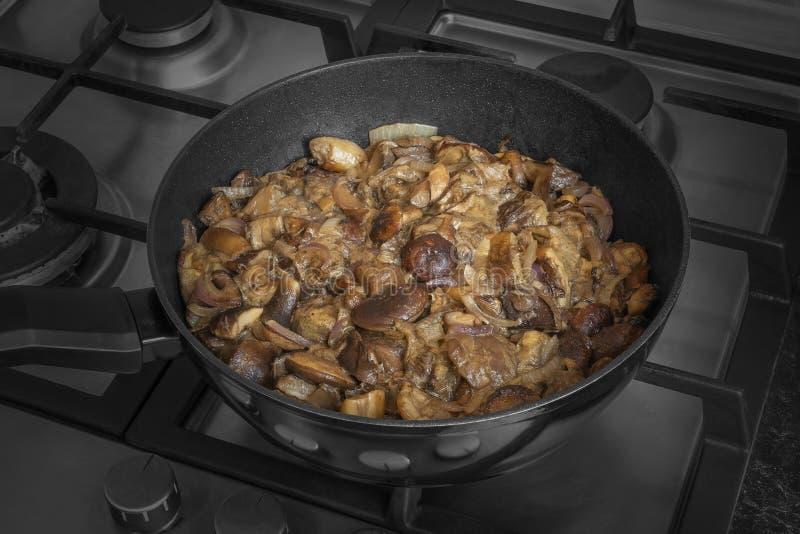 Setas del badia de Fried Imleria en un sartén Badius cocinado del boleto con la cebolla en la plancha imagen de archivo