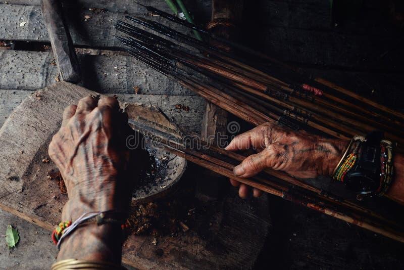 Setas tribais do envenenamento de Toikot da pessoa idosa para caçar em sua casa da selva fotografia de stock